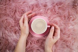 Female hands and coffee cup on pink