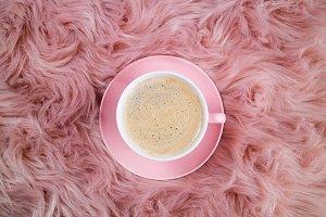 Coffee cup on pink woolen fur
