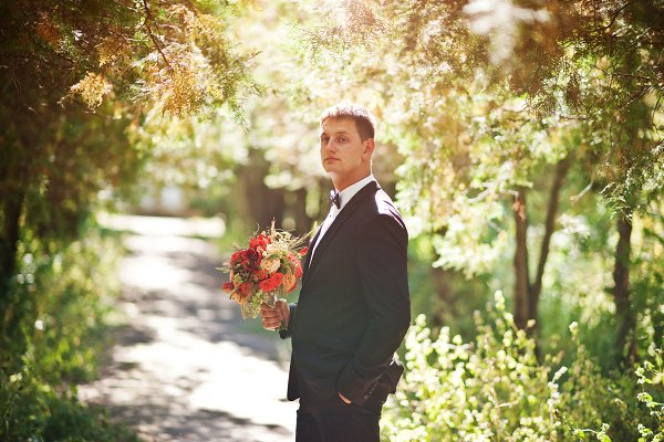 Portrait of a handsome groom holdin…