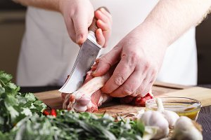 Butcher cutting lamb meat on kitchen