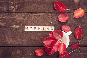 Red leaves, word MORNING and wooden