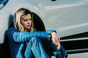 scared young woman sitting near car