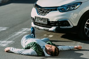 injured young man and car on road af