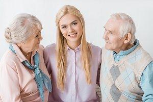 young smiling woman hugging senior p