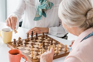 senior women playing chess and drink