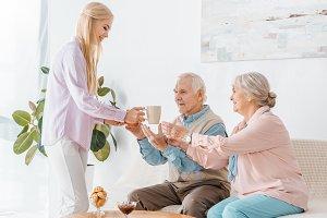 young woman giving senior parents cu