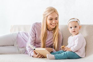 young smiling mother reading book to