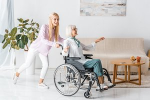 young woman pushing wheelchair with
