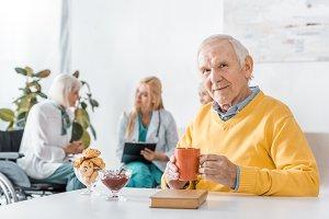 senior man drinking tea while doctor
