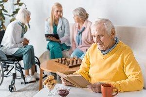 senior man reading book while female