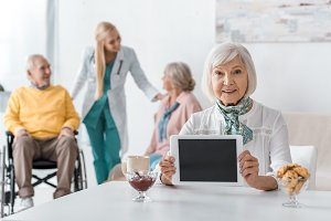 senior woman holding digital tablet