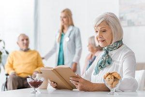 senior woman reading book at nursing