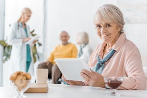senior woman using digital tablet at