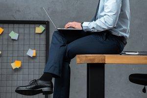 confident businessman sitting on tab