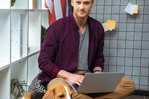 happy male freelancer working on lap