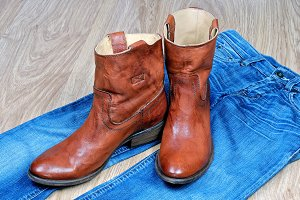 Brown cowboy boots on blue jeans