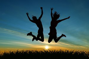 Two girls jumping for joy at sunset