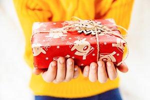 Child holds a Christmas decor and gi