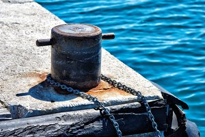 Old metal rusty mooring bollard with
