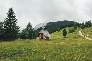 Small wooden church on the meadow