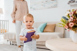 adorable toddler holding book and lo