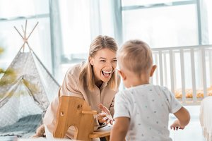 happy mother and toddler playing wit