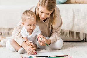 mother and adorable toddler drawing