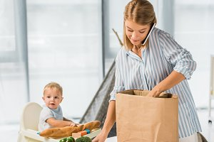 mother holding groceries while talki
