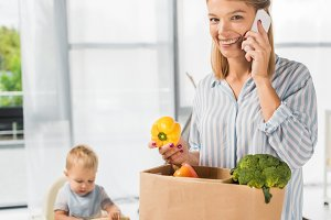 smiling mother holding groceries whi