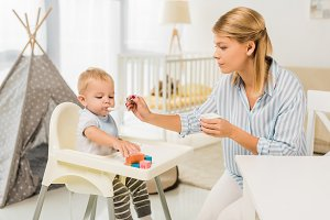 mother feeding son in highchair with