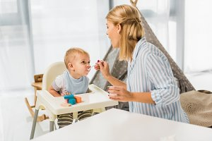 mom feeding son in highchair with ba