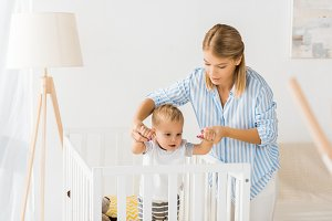 mom holding hands of son in crib in
