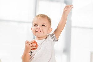 cute toddler raising hand and sittin