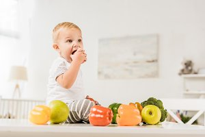 cute toddler eating and sitting on t