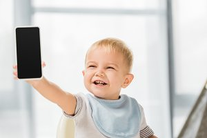 cute smiling toddler holding smartph