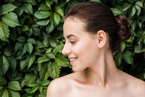 smiling young woman with green leave