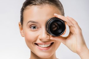 young smiling woman holding lens nea