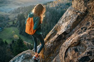 woman is standing on edge of cliff