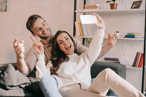 happy young couple taking selfie wit