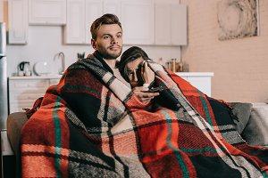 young couple relaxing on couch and w