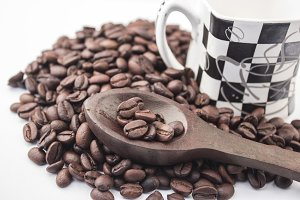 Coffee beans on white with cup