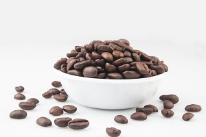 Coffee beans in a bowl on white