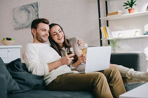 laughing young couple using laptop a