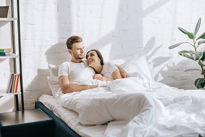happy young couple relaxing in bed i