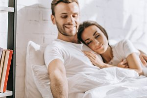 happy young man relaxing in bed with