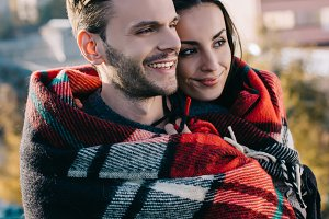 happy young couple covering in plaid