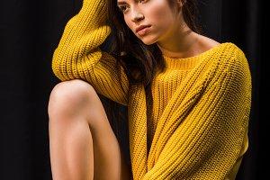 pensive woman in yellow woolen sweat