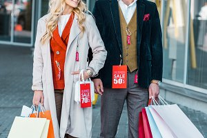 elegant fashionable couple with shop