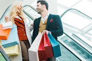 happy stylish couple with shopping b