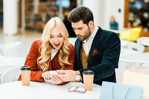 excited couple using smartphone in c